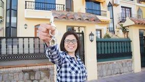 Mujer joven feliz con llaves de la nueva casa al aire libre metrajes