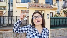 Mujer joven feliz con llaves de la nueva casa al aire libre almacen de video
