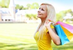 Mujer joven feliz con los bolsos de compras outdoor Foto de archivo libre de regalías