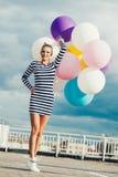 Mujer joven feliz con los globos coloridos del látex Imagenes de archivo