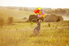 Mujer joven feliz con los globos entre un campo Fotos de archivo libres de regalías