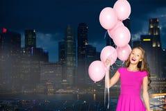 Mujer joven feliz con los globos sobre ciudad de la noche Fotografía de archivo libre de regalías