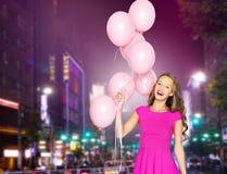 Mujer joven feliz con los globos sobre ciudad de la noche Imágenes de archivo libres de regalías
