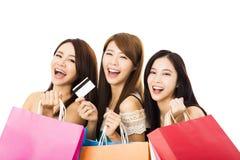 Mujer joven feliz con los panieres y la tarjeta de crédito Imagen de archivo libre de regalías