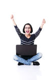Mujer joven feliz que usa su ordenador portátil Imágenes de archivo libres de regalías