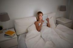 Mujer joven feliz con PC de la tableta en cama en casa Imágenes de archivo libres de regalías