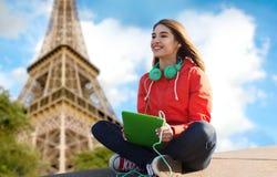 Mujer joven feliz con PC y los auriculares de la tableta Imágenes de archivo libres de regalías