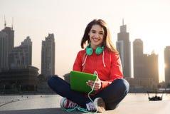 Mujer joven feliz con PC y los auriculares de la tableta Foto de archivo libre de regalías