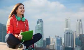 Mujer joven feliz con PC y los auriculares de la tableta Fotos de archivo