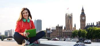 Mujer joven feliz con PC y los auriculares de la tableta Imagenes de archivo
