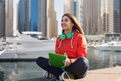 Mujer joven feliz con PC y los auriculares de la tableta Imagen de archivo