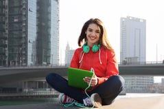 Mujer joven feliz con PC y los auriculares de la tableta Fotografía de archivo