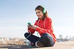 Mujer joven feliz con smartphone y los auriculares Foto de archivo