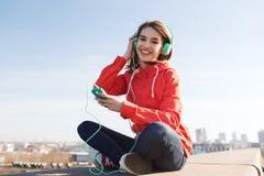 Mujer joven feliz con smartphone y los auriculares Imágenes de archivo libres de regalías