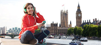 Mujer joven feliz con smartphone y los auriculares Foto de archivo libre de regalías