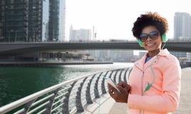 Mujer joven feliz con smartphone y los auriculares Imagen de archivo libre de regalías