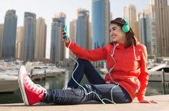 Mujer joven feliz con smartphone y los auriculares Fotografía de archivo libre de regalías