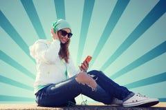 Mujer joven feliz con smartphone y los auriculares Fotografía de archivo