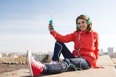 Mujer joven feliz con smartphone y los auriculares Imagen de archivo