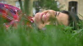 Mujer joven feliz con sonrisa hermosa con los dientes que mienten en la hierba, d3ia hermoso soleado de la naturaleza al aire lib metrajes