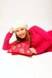 Mujer joven feliz con un casquillo y una mentira de la almohada   Imagen de archivo