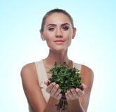 Mujer joven feliz con un paquete de menta fresca. Vegetaria del concepto Imagen de archivo libre de regalías