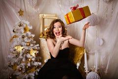Mujer joven feliz con un regalo de la Navidad Imagenes de archivo