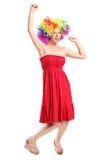 Mujer joven feliz con una peluca que gesticula alegría Imagen de archivo