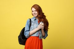 Mujer joven feliz con una taza de café disponible sobre fondo amarillo brillante aislado Fotografía de archivo libre de regalías