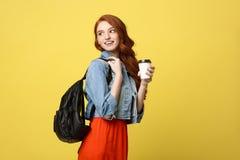 Mujer joven feliz con una taza de café disponible sobre fondo amarillo brillante aislado Imagen de archivo