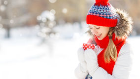 Mujer joven feliz con una taza de té caliente en paseo del invierno Fotos de archivo libres de regalías