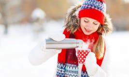 Mujer joven feliz con una taza de té caliente en paseo del invierno Imágenes de archivo libres de regalías