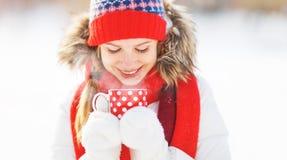 Mujer joven feliz con una taza de té caliente en paseo del invierno Foto de archivo libre de regalías
