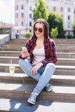 Mujer joven feliz con una taza fresca que se sienta en las escaleras y que usa su smartphone Imagen de archivo libre de regalías