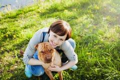 Mujer joven feliz de risa en los guardapolvos del dril de algodón que abrazan su perro lindo rojo Shar Pei en la hierba verde en  Imagen de archivo