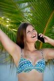 Mujer joven feliz debajo de la palmera que habla en el tel?fono elegante fotos de archivo