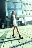 Mujer joven feliz del éxito que camina en luz del sol de la ciudad Foto de archivo
