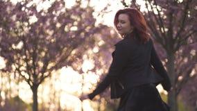 Mujer joven feliz del bailar?n del viaje que disfruta del tiempo libre en un parque de la flor de cerezo de Sakura - muchacha bla metrajes