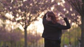 Mujer joven feliz del bailar?n del viaje que disfruta del tiempo libre en un parque de la flor de cerezo de Sakura - muchacha bla almacen de video