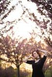 Mujer joven feliz del bailar?n del viaje que disfruta del tiempo libre en un parque de la flor de cerezo de Sakura - muchacha bla imagen de archivo