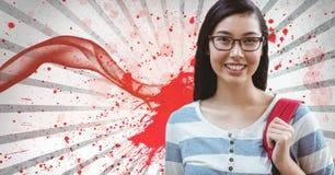 Mujer joven feliz del estudiante que se opone al fondo salpicado blanco y rojo Imagen de archivo
