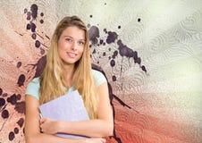 Mujer joven feliz del estudiante que sostiene carpetas contra el fondo salpicado del blanco, rojo y púrpura Imágenes de archivo libres de regalías