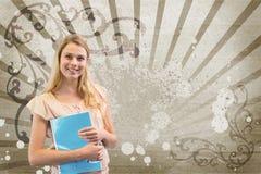 Mujer joven feliz del estudiante que sostiene un cuaderno contra fondo salpicado marrón y blanco Foto de archivo