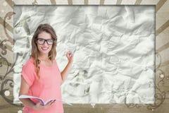 Mujer joven feliz del estudiante que sostiene un cuaderno contra fondo salpicado marrón y blanco Fotografía de archivo libre de regalías
