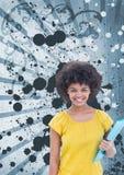 Mujer joven feliz del estudiante que sostiene una carpeta contra fondo salpicado azul Fotos de archivo