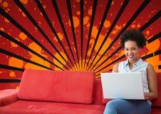 Mujer joven feliz del estudiante que usa un ordenador contra el fondo salpicado del rojo, negro y anaranjado Fotos de archivo libres de regalías