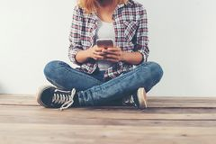 Mujer joven feliz del inconformista que se sienta en el piso de madera que mecanografía en smar Fotografía de archivo libre de regalías