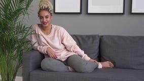 Mujer joven feliz del inconformista que sonríe mientras que se sienta en el sofá cómodo en casa almacen de metraje de vídeo