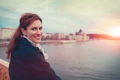 Mujer joven feliz del pelirrojo que considera detrás el paisaje urbano de Budapest adentro imagen de archivo libre de regalías