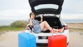 Mujer joven feliz el las vacaciones del viaje del verano que se sientan en un tronco de coche metrajes
